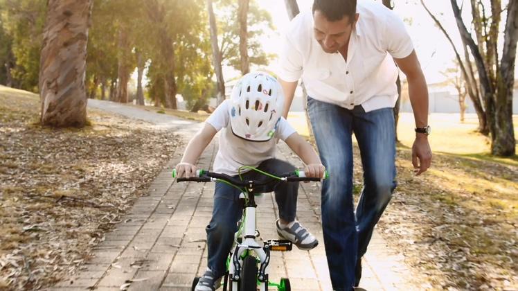 跟踪拍摄的父亲教他的儿子如何骑自行车