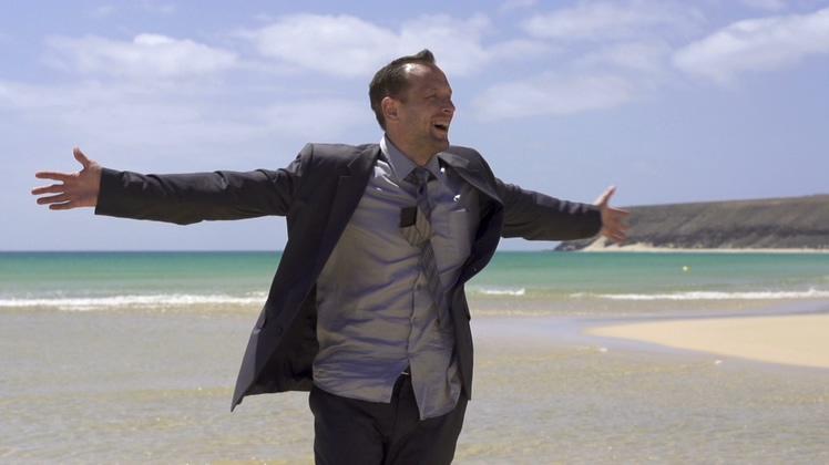 兴奋快乐男人在海滩上张开双臂庆祝