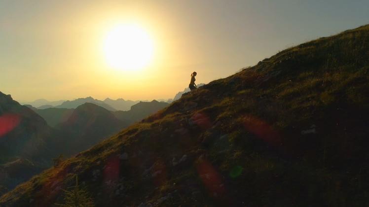 独行迎着日出阳光攀登山峰