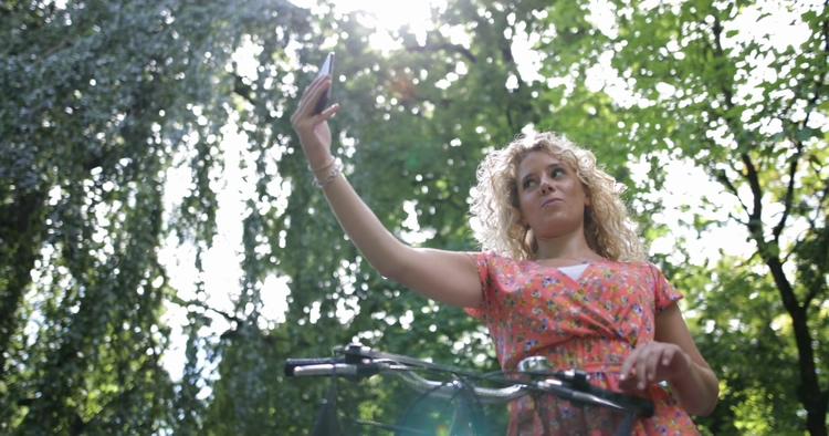 骑自行车的成年女性在阳光下手机拍照自拍