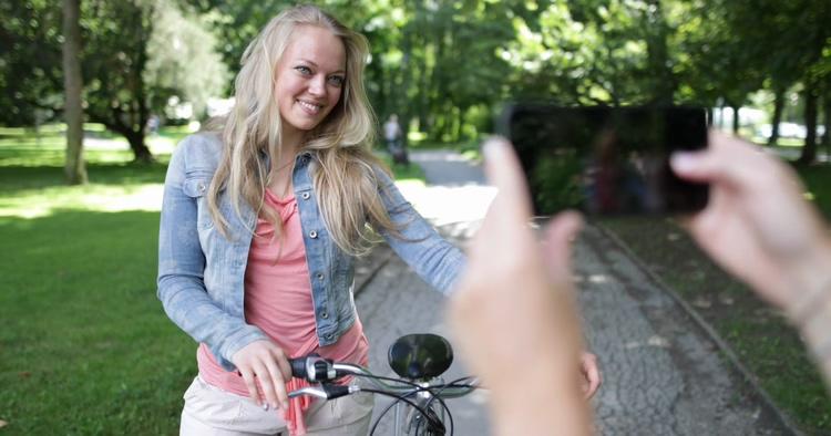 在公园树林里拿起手机给骑自行车的女性拍照