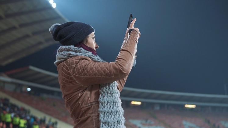 美女在体育场拿着平板拍照摄像