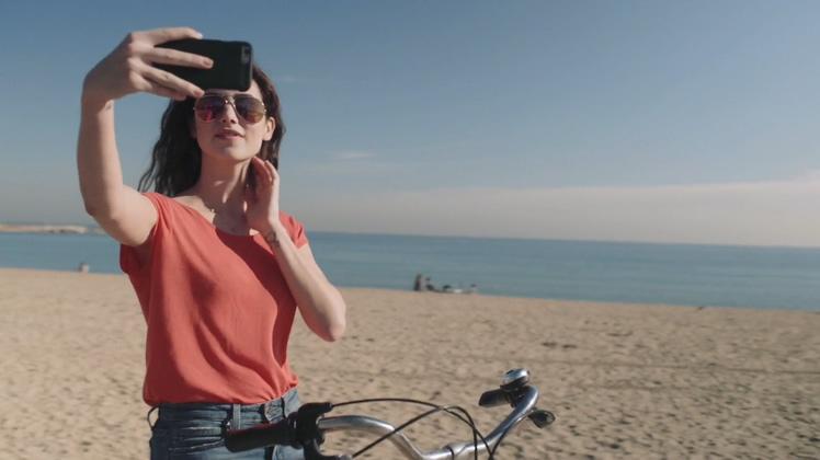 一个美女骑自行车在海边沙滩上自拍