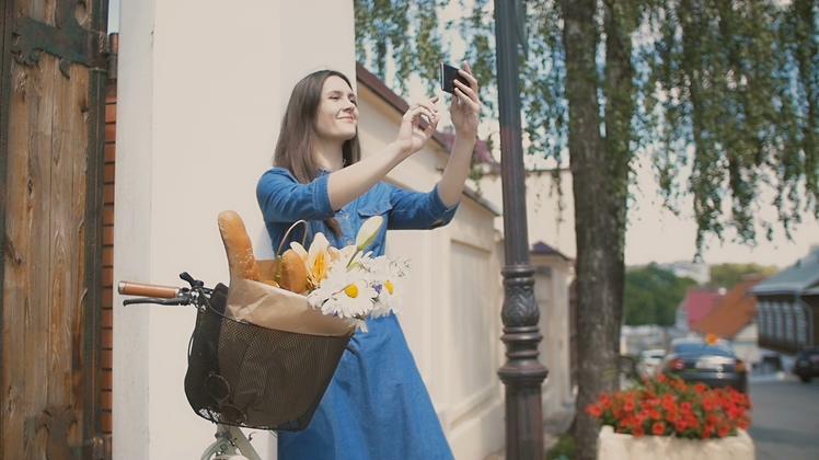 欧美,女性,美女,骑自行车,面包,手机,自拍,拍照,一个美女骑着自行车在欧式风光城市自拍视频素材