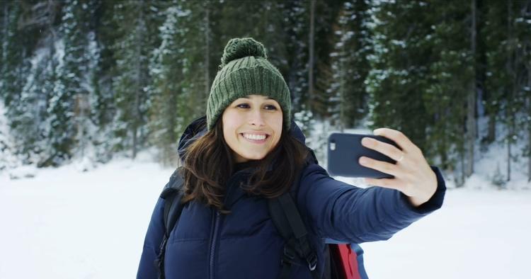 一个美女雪地旅行在森林里自拍