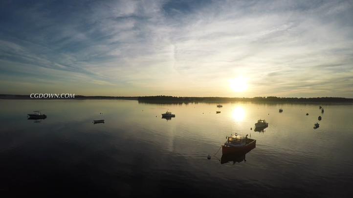 在夕阳落日的湖面上停靠着小船实拍素材