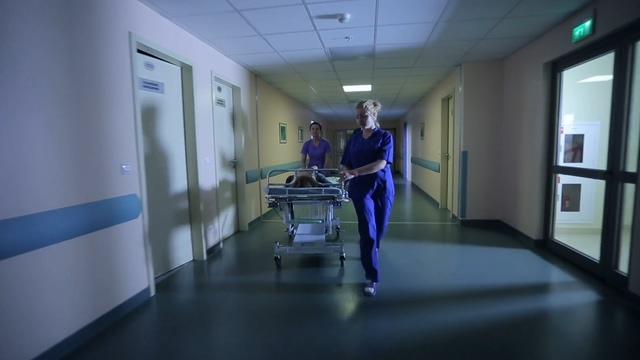 在医院医务人员推着病人病床在医药走廊里行走
