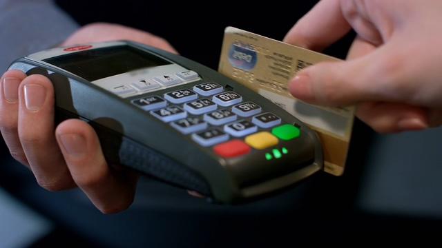 POS机,刷卡,银行卡,消费,交易,在手持pso机上拿着银行卡刷卡消费视频素材