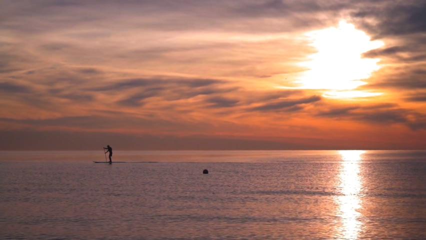 在美丽晚霞大海上滑独木舟