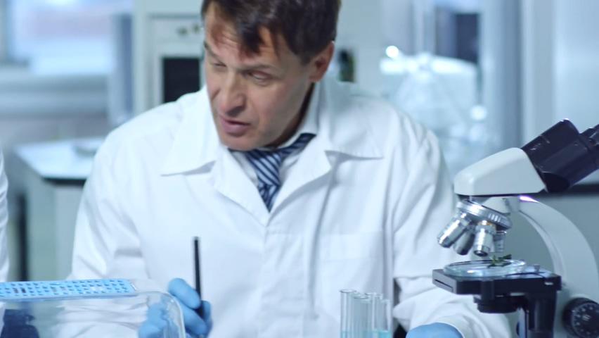 三名化学家在实验室工作并研究化学反应的镜头视频素材影视模板