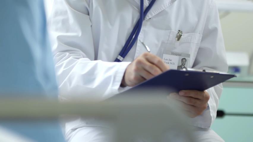 男医生在写笔记在剪贴板上和使用听诊器女病人