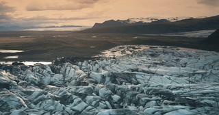 日落时在冰盐水湖的火山灰的冰川航拍