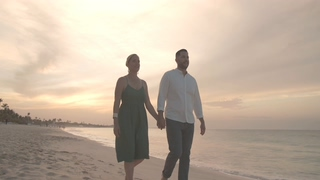 情侣,爱情,牵手,慢镜头拍摄情侣牵着手在日落海滩散步视频素材