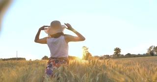 在阳光明媚的一天,一个女人正沿着麦田与一条白色连衣裙,戴着草帽在自然背景上概念生活方式生态环境快乐的视频素材